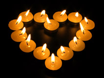 Glowing candles arranged in a heart